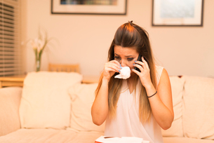 Young woman having telephone conversation, cryingの写真素材 [FYI03523894]