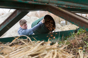 Teenage boy emptying garden waste into recycling binの写真素材 [FYI03524040]