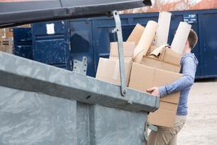 Teenage boy carrying cardboard waste to recycling binの写真素材 [FYI03524042]