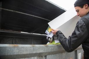 Teenage boy emptying bin with paper waste to recycling binの写真素材 [FYI03524044]