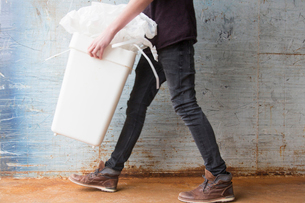 Teenage boy carrying bin with recyclable paper wasteの写真素材 [FYI03524046]