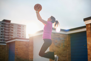 Mature female basketball player catching ball mid airの写真素材 [FYI03524120]
