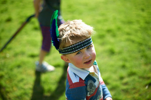 Portrait of  young boy wearing headband with feathersの写真素材 [FYI03524126]