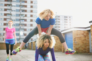 Three women exercising together wearing sports clothing and playing leap frogの写真素材 [FYI03524443]