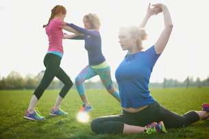 Three women exercising and stretching in the parkの写真素材 [FYI03524451]