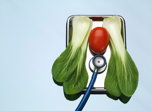 Stethoscope on medical tray with a tomato and pak choi illustrating healthy lungs and heartの写真素材 [FYI03524585]