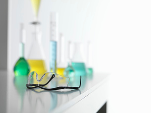 Safety glasses on laboratory bench with a chemical experiment in backgroundの写真素材 [FYI03524601]