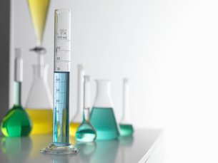 Laboratory glassware on lab bench with a graduated measuring cylinder in foregroundの写真素材 [FYI03524603]
