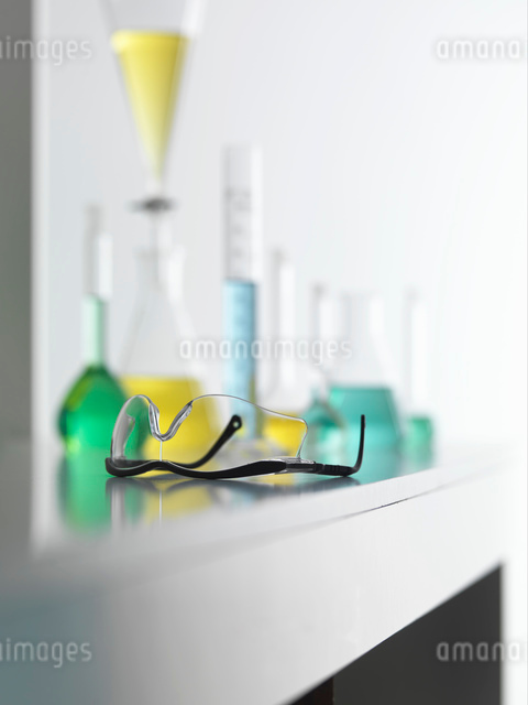 Laboratory safety glasses on lab bench with a chemical experiment in backgroundの写真素材 [FYI03524605]