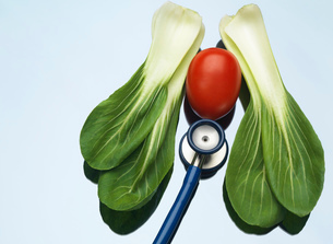 Stethoscope on a medical tray with a tomato and pak choi to illustrate  healthy lungs and heartの写真素材 [FYI03524617]