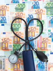 Blood pressure gauge on top of euro currency notes, tubes twisted into heart shapeの写真素材 [FYI03524675]