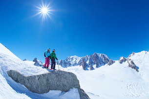 Male and female skiers looking out from ridge on Mont Blanc massif, Graian Alps, Franceの写真素材 [FYI03524699]