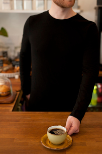 Cropped shot of cafe waiter serving fresh coffeeの写真素材 [FYI03524755]
