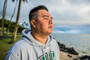 Young man looking out at sunrise from Kaaawa beach, Oahu, Hawaii, USAの写真素材 [FYI03524777]