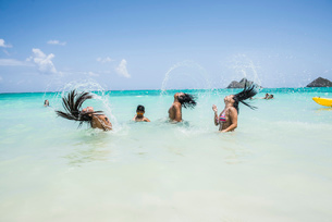 Side view of young women throwing long wet hair back in sea at Lanikai Beach, Oahu, Hawaii, USAの写真素材 [FYI03524798]