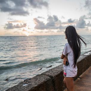Young woman watching sunrise, Kaaawa beach, Oahu, Hawaii, USAの写真素材 [FYI03524811]