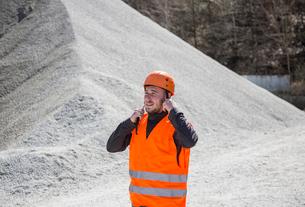 Quarry worker fastening helmet at gravel quarryの写真素材 [FYI03524923]
