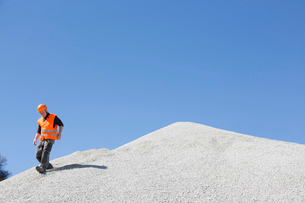Quarry worker moving down steep gravel mound at quarryの写真素材 [FYI03524924]