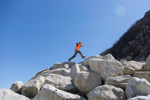 Worker jumping on stack of boulders at quarryの写真素材 [FYI03524925]