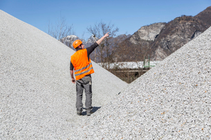 Quarry worker pointing from gravel mounds at quarryの写真素材 [FYI03524926]