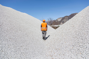 Quarry worker walking through gravel mounds at quarryの写真素材 [FYI03524927]