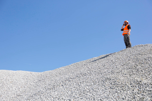 Quarry worker chatting on smartphone from quarry gravel moundの写真素材 [FYI03524928]