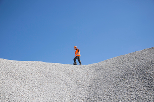 Quarry worker chatting on smartphone on top of quarry gravel moundの写真素材 [FYI03524931]