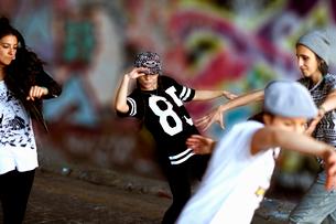 Young women breakdancing against street artの写真素材 [FYI03525229]
