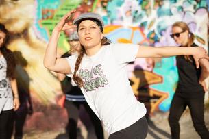 Young women breakdancing, arms raised, looking awayの写真素材 [FYI03525234]