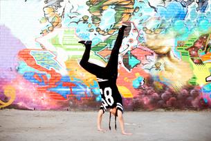 Young women in handstand breakdancing freeze against graffitiの写真素材 [FYI03525241]