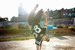 Young women doing upside down breakdancing freeze, looking at cameraの写真素材 [FYI03525244]