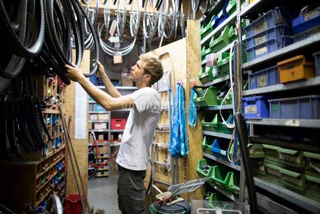 Mid adult man in repair shop choosing bicycle tyreの写真素材 [FYI03525312]
