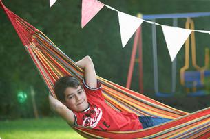 Portrait of confident boy reclining in striped garden hammock with hands behind headの写真素材 [FYI03525455]