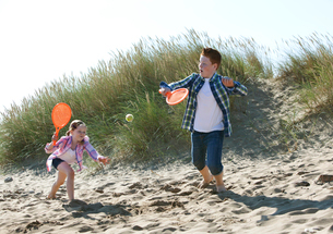 Girl and boy playing with orange sports bat and tennis ball on dunesの写真素材 [FYI03525470]