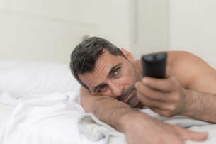 Bare shouldered mature man lying on front on bed using remote controlの写真素材 [FYI03525483]