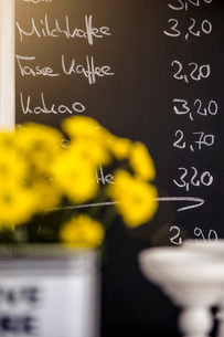 Yellow flowers in front of cafes chalkboard menu, focus on backgroundの写真素材 [FYI03525494]