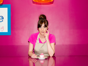Young woman, working in cake shop, sitting with cupcake in front of herの写真素材 [FYI03525729]