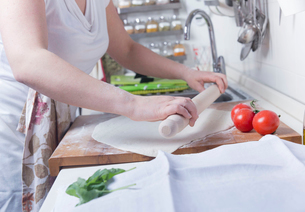 Cropped shot of woman rolling out pastry on kitchen counterの写真素材 [FYI03525840]
