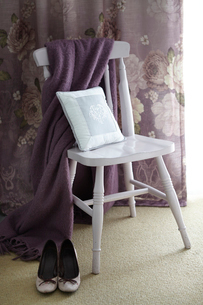 High heels, shawl and cushion on chair, curtain in backgroundの写真素材 [FYI03525913]