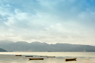 Tranquil view of moored fishing boats on Lugu Lake, Yunnan, Chinaの写真素材 [FYI03526403]