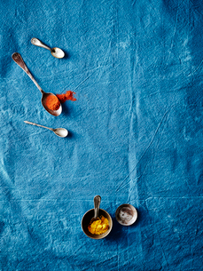Overhead view of spoonfuls of turmeric and paprika spices on blue backgroundの写真素材 [FYI03526460]