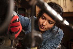 Female mechanic working on motorcycle in workshopの写真素材 [FYI03526595]