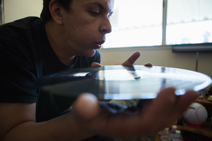 Close up of young man blowing surface of vinyl recordの写真素材 [FYI03526624]