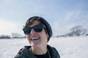 Portrait of mid adult woman, laughing, against snowy backdropの写真素材 [FYI03526627]