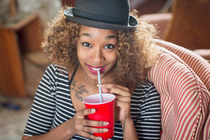 Portrait of young woman wearing fedora and drinking soft drinkの写真素材 [FYI03526687]