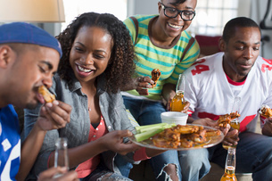 Group of adult friends eating takeaway on living room sofaの写真素材 [FYI03526699]