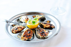 Barbecued oysters with lemon on restaurant tableの写真素材 [FYI03526757]