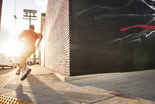 Rear view of male runner running on sidewalkの写真素材 [FYI03526919]