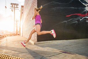 Female runner running along sidewalkの写真素材 [FYI03526920]