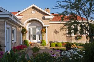 Beige brick house exterior with front door portico and flower bed gardenの写真素材 [FYI03526946]